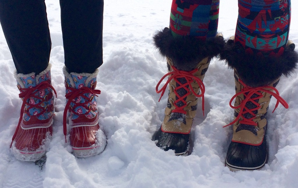cropped photo of two people wearing boots in the snow