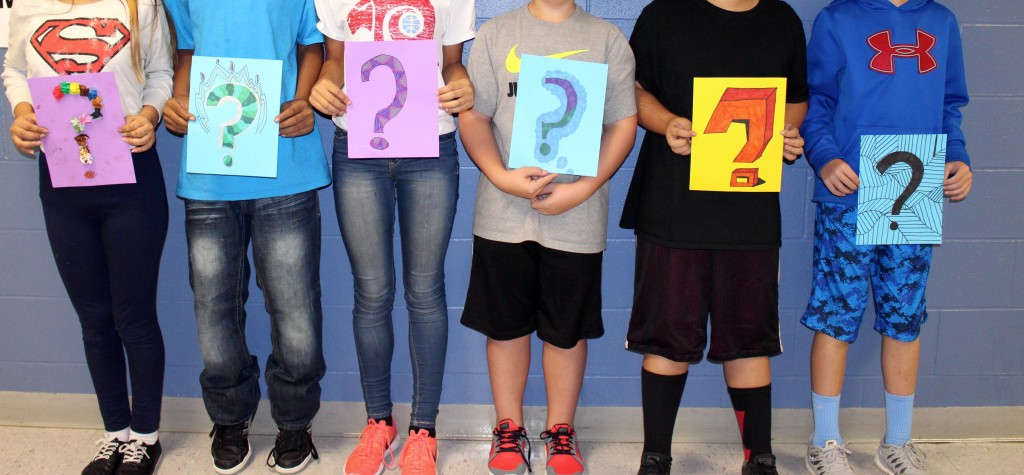 students holding question mark signs