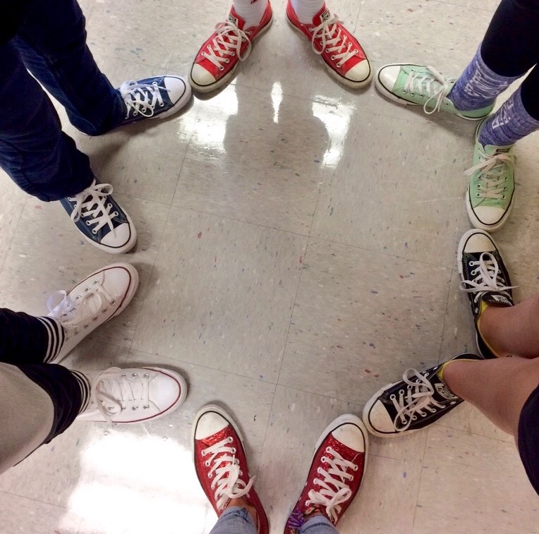 circle of people all wearing same shoes