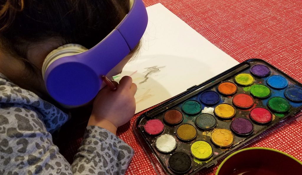 student painting while listening