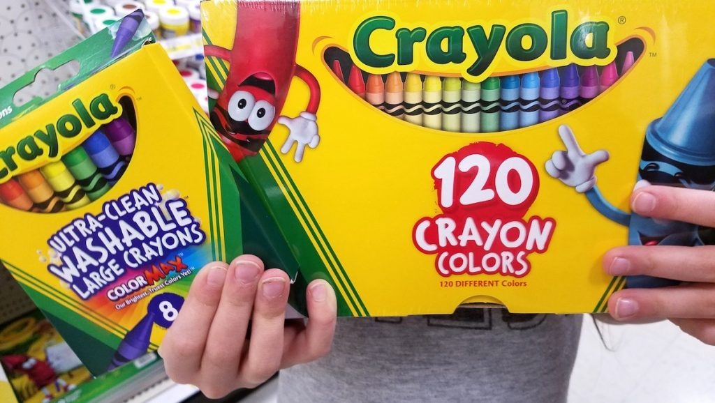 kid holding crayons