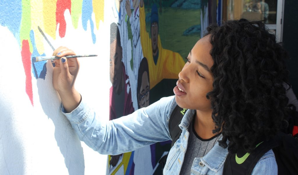 student working on mural