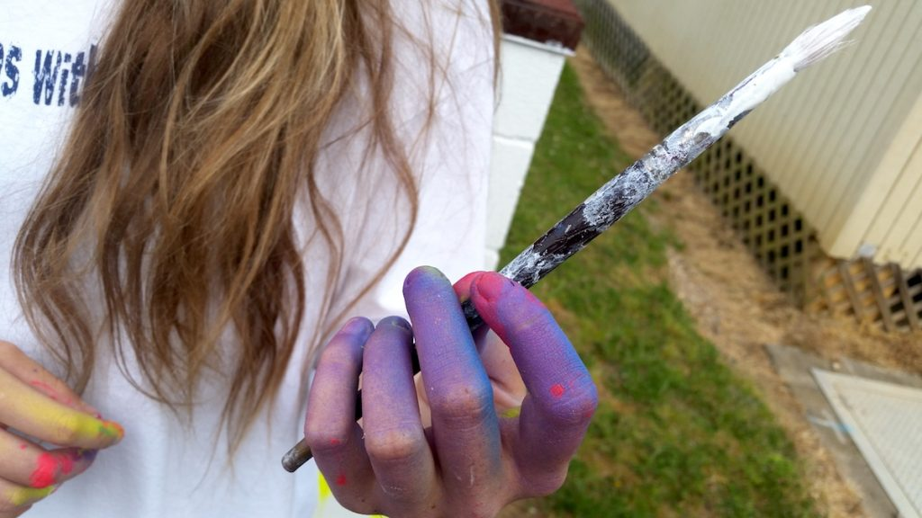 student with painty hand