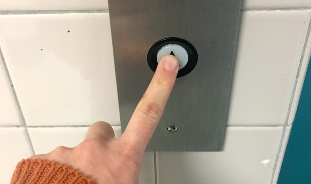 person pushing elevator button