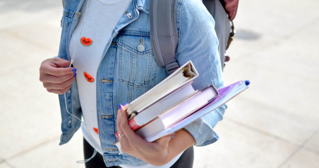teen walking with books