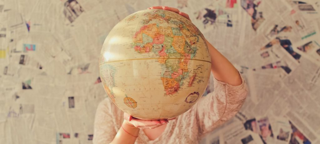 person holding globe in front of their face