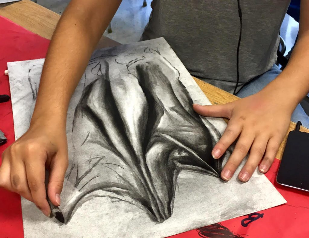 student working on charcoal drawing