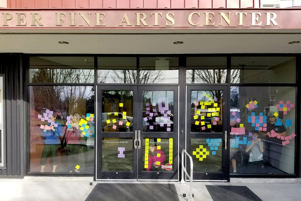 students working on sticky note mural