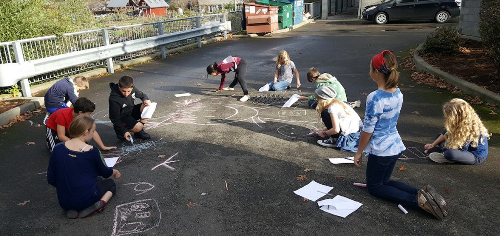 students working with chalk outside
