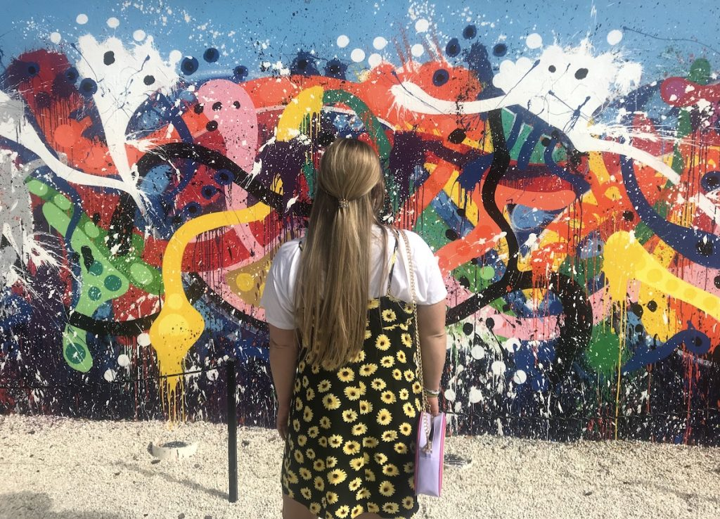 woman standing in front of mural