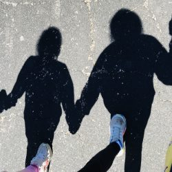 Image of the shadows of an adult holding hands with children