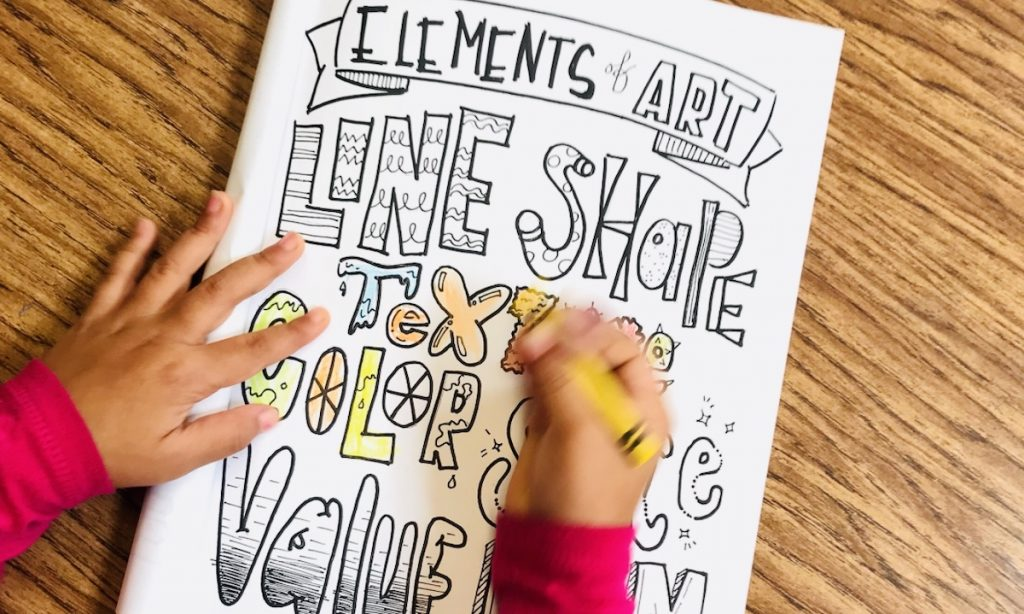 Students drawing in a coloring sheet