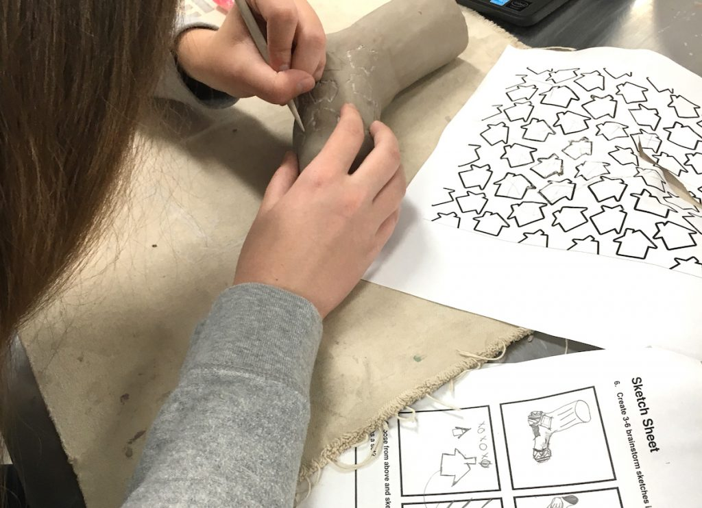 Student working on clay artwork