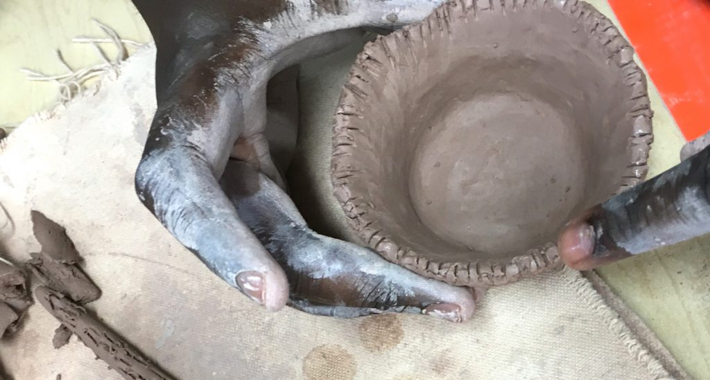 Hands making bowl out of clay