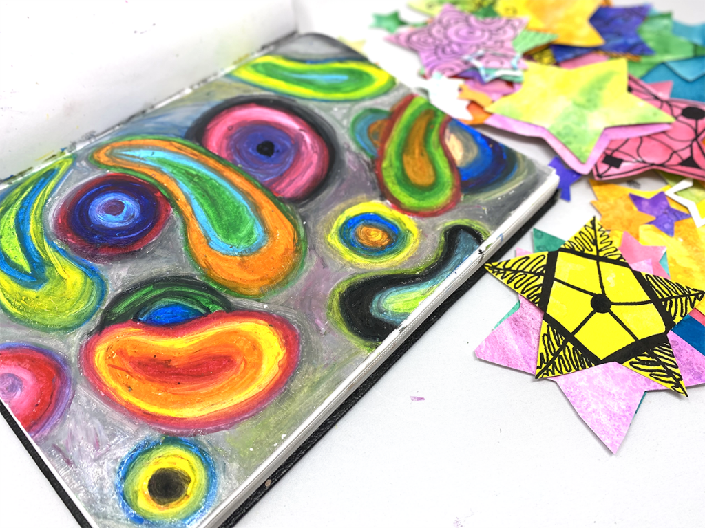 abstract oil pastel design in sketchbook with paper stars