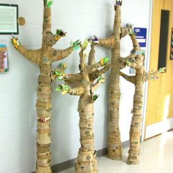 four tall trees made of coffee sleeve cardboard pieces in school hallway